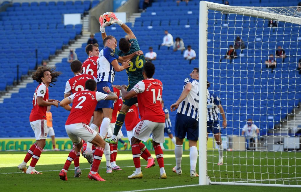 Arsenal's Argentinian goalkeeper Emiliano Martinez catches the ball despite pressure from Brighton's English defender Dan Burn during the English Premier League football match between Brighton and Hove Albion and Arsenal at the American Express Community Stadium in Brighton, southern England on June 20, 2020. (Photo by Mike Hewitt / POOL / AFP) / RESTRICTED TO EDITORIAL USE. No use with unauthorized audio, video, data, fixture lists, club/league logos or 'live' services. Online in-match use limited to 120 images. An additional 40 images may be used in extra time. No video emulation. Social media in-match use limited to 120 images. An additional 40 images may be used in extra time. No use in betting publications, games or single club/league/player publications. / (Photo by MIKE HEWITT/POOL/AFP via Getty Images)