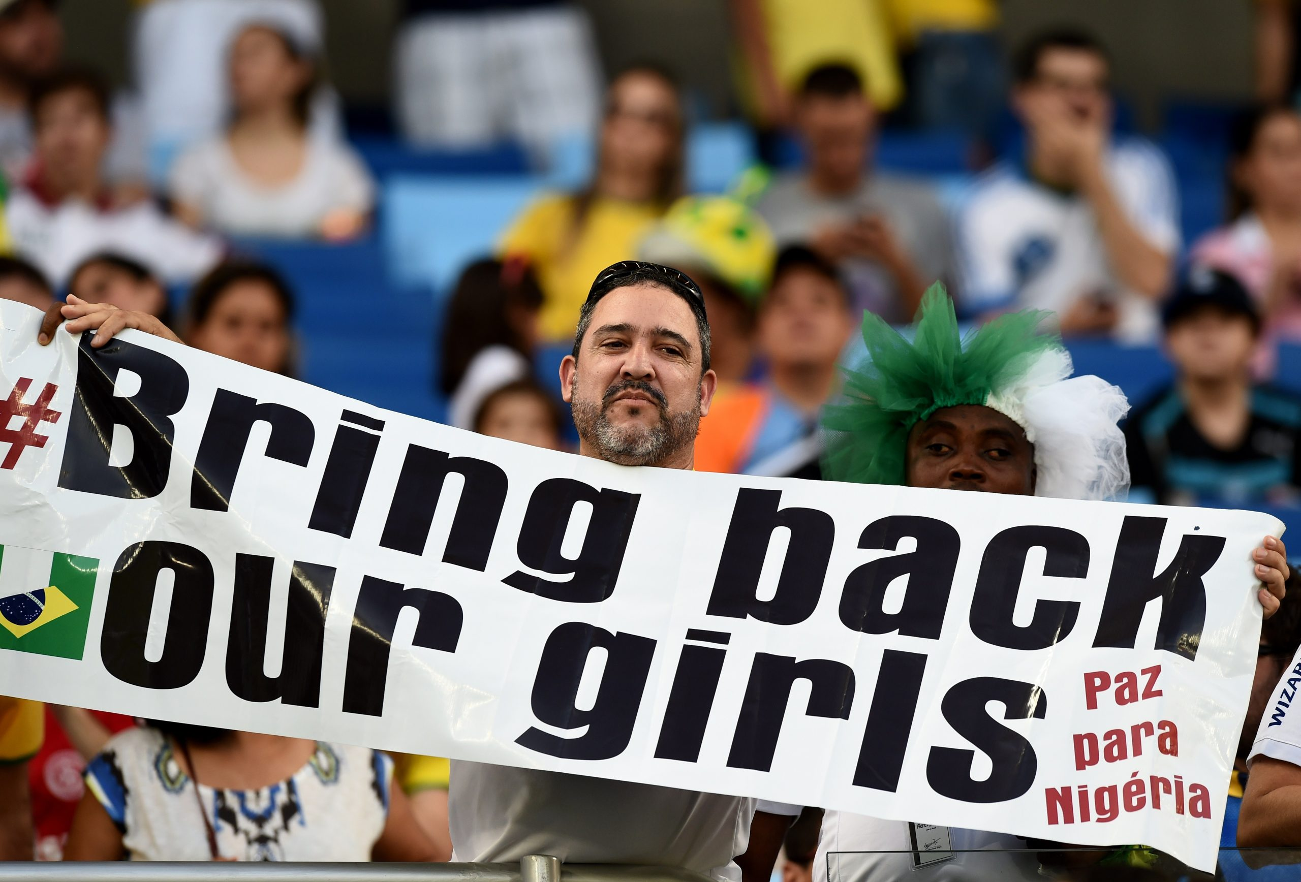 "A man holds a banner ""Bring back our girls"" before the Group F football match between Nigeria and Bosnia-Hercegovina at the Pantanal Arena in Cuiaba during the 2014 FIFA World Cup on June 21, 2014.   AFP PHOTO / JEWEL SAMAD"