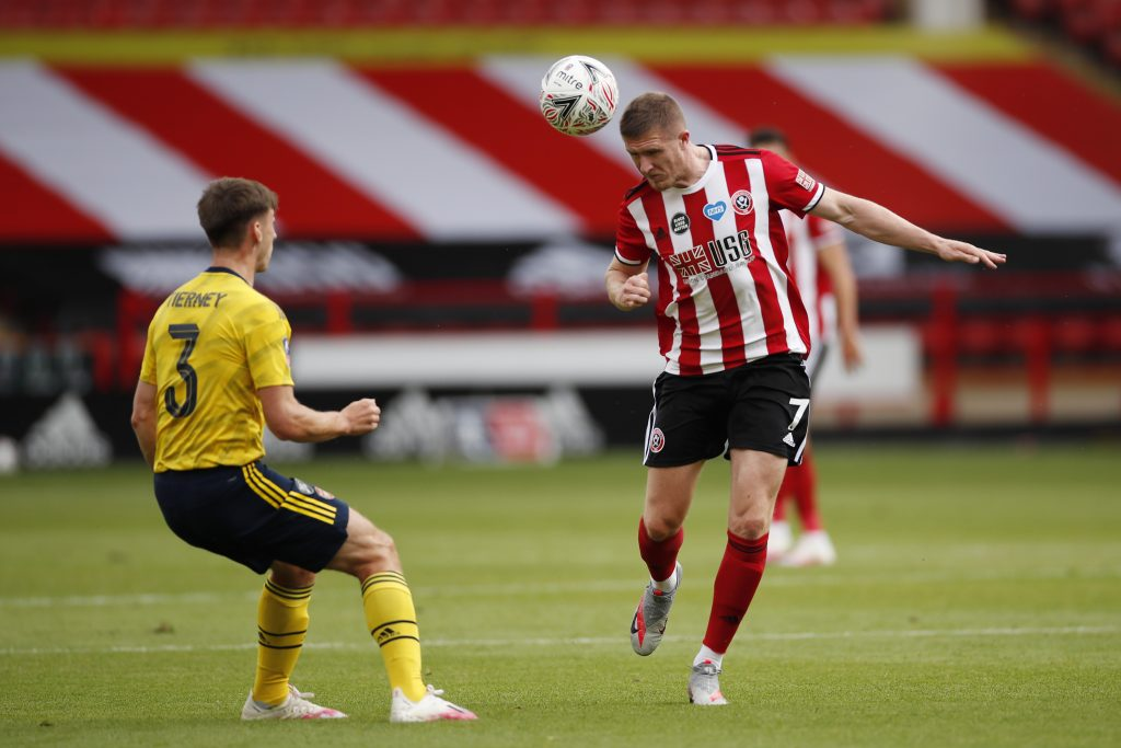 SHEFFIELD, ENGLAND - JUNE 28: John Lundstram of Sheffield United wins a header over Kieran Tierney of Arsenal during the FA Cup Fifth Quarter Final match between Sheffield United and Arsenal FC at Bramall Lane on June 28, 2020 in Sheffield, England. (Photo by Andrew Boyers/Pool via Getty Images)