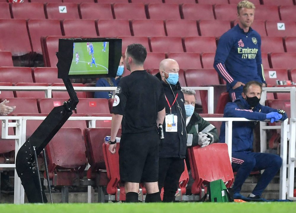 LONDON, ENGLAND - JULY 07: Match Referee, Chris Kavanagh checks a VAR decision on screen ahead of showing Eddie Nketiah of Arsenal (not pictured) a red card during the Premier League match between Arsenal FC and Leicester City at Emirates Stadium on July 07, 2020 in London, England. Football Stadiums around Europe remain empty due to the Coronavirus Pandemic as Government social distancing laws prohibit fans inside venues resulting in all fixtures being played behind closed doors. (Photo by Michael Regan/Getty Images)