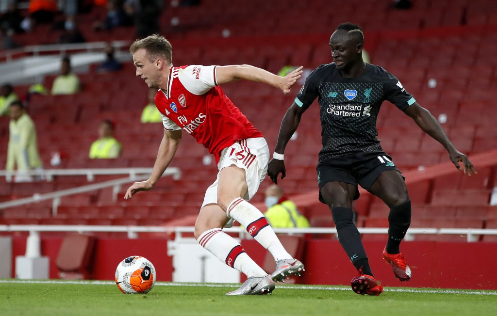 LONDON, ENGLAND - JULY 15: Rob Holding of Arsenal is challenged by Sadio Mane of Liverpool during the Premier League match between Arsenal FC and Liverpool FC at Emirates Stadium on July 15, 2020 in London, England. Football Stadiums around Europe remain empty due to the Coronavirus Pandemic as Government social distancing laws prohibit fans inside venues resulting in all fixtures being played behind closed doors. (Photo by Paul Childs/Pool via Getty Images)