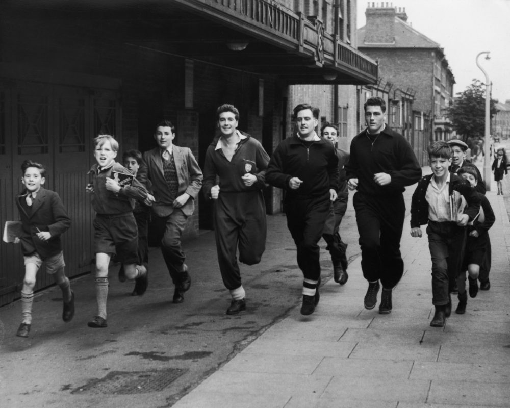 The schoolboy fans have fun running in the streets around Highbury Stadium with members of the Arsenal football team, (left to right), Wilkins, David Bowen and Cliff Holton, 25th July 1954. (Photo by William Vanderson/Fox Photos/Hulton Archive/Getty Images)