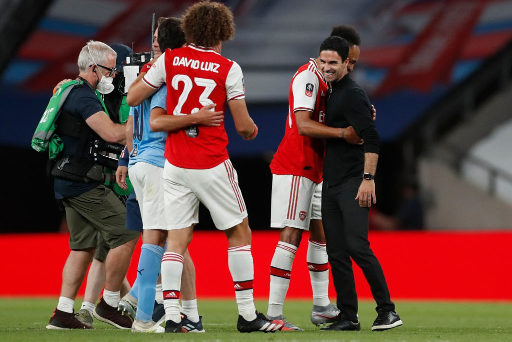 Arsenal's Spanish head coach Mikel Arteta (R) embraces Arsenal's Gabonese striker Pierre-Emerick Aubameyang (2R) at the end of the English FA Cup semi-final football match between Arsenal and Manchester City at Wembley Stadium in London, on July 18, 2020. (Photo by MATTHEW CHILDS / POOL / AFP)