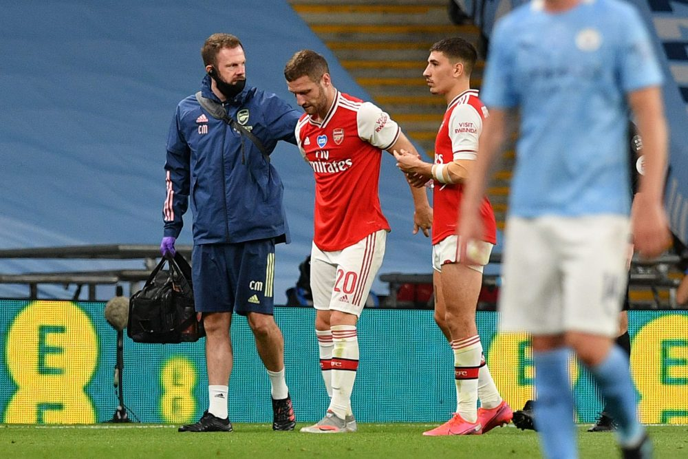 Arsenal's German defender Shkodran Mustafi (C) is helped off the pitch injured during the English FA Cup semi-final football match between Arsenal and Manchester City at Wembley Stadium in London, on July 18, 2020. (Photo by JUSTIN TALLIS / POOL / AFP)