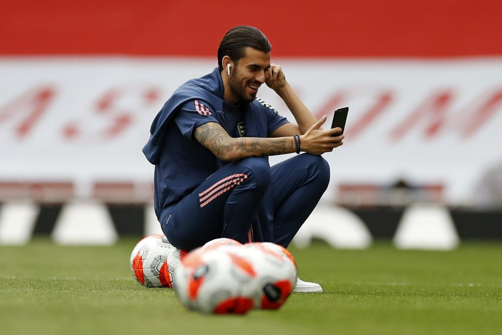 Arsenal's Spanish midfielder Dani Ceballos smiles as he checks his phone on the pitch ahead of the English Premier League football match between Arsenal and Liverpool at the Emirates Stadium in London on July 15, 2020. (Photo by PAUL CHILDS/POOL/AFP via Getty Images)