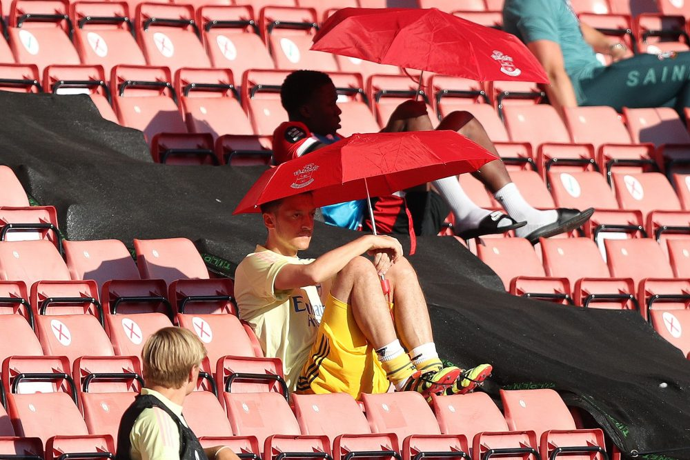 Arsenal's German midfielder Mesut Ozil (C) shelters from the sunshine beneath an umbrella during the English Premier League football match between Southampton and Arsenal at St Mary's Stadium in Southampton, southern England on June 25, 2020. (Photo by Andrew Matthews / POOL / AFP)