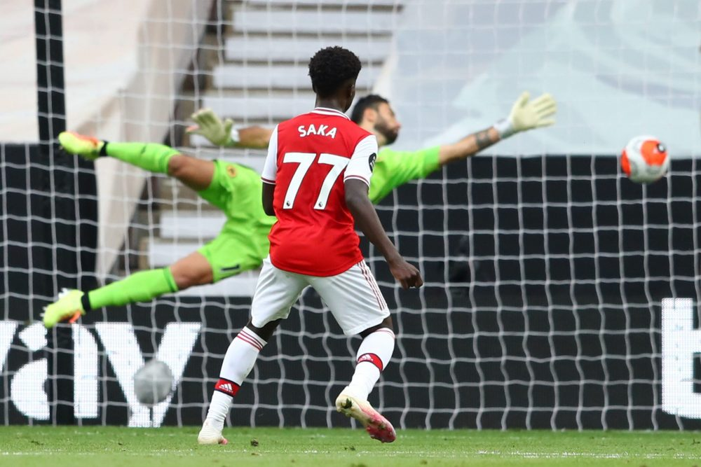 Arsenal's English striker Bukayo Saka watches his shot beat Wolverhampton Wanderers' Portuguese goalkeeper Rui Patricio to score the opening goal during the English Premier League football match between Wolverhampton Wanderers and Arsenal at the Molineux stadium in Wolverhampton, central England on July 4, 2020. (Photo by Michael Steele / POOL / AFP) / RESTRICTED TO EDITORIAL USE. No use with unauthorized audio, video, data, fixture lists, club/league logos or 'live' services. Online in-match use limited to 120 images. An additional 40 images may be used in extra time. No video emulation. Social media in-match use limited to 120 images. An additional 40 images may be used in extra time. No use in betting publications, games or single club/league/player publications. / (Photo by MICHAEL STEELE/POOL/AFP via Getty Images)