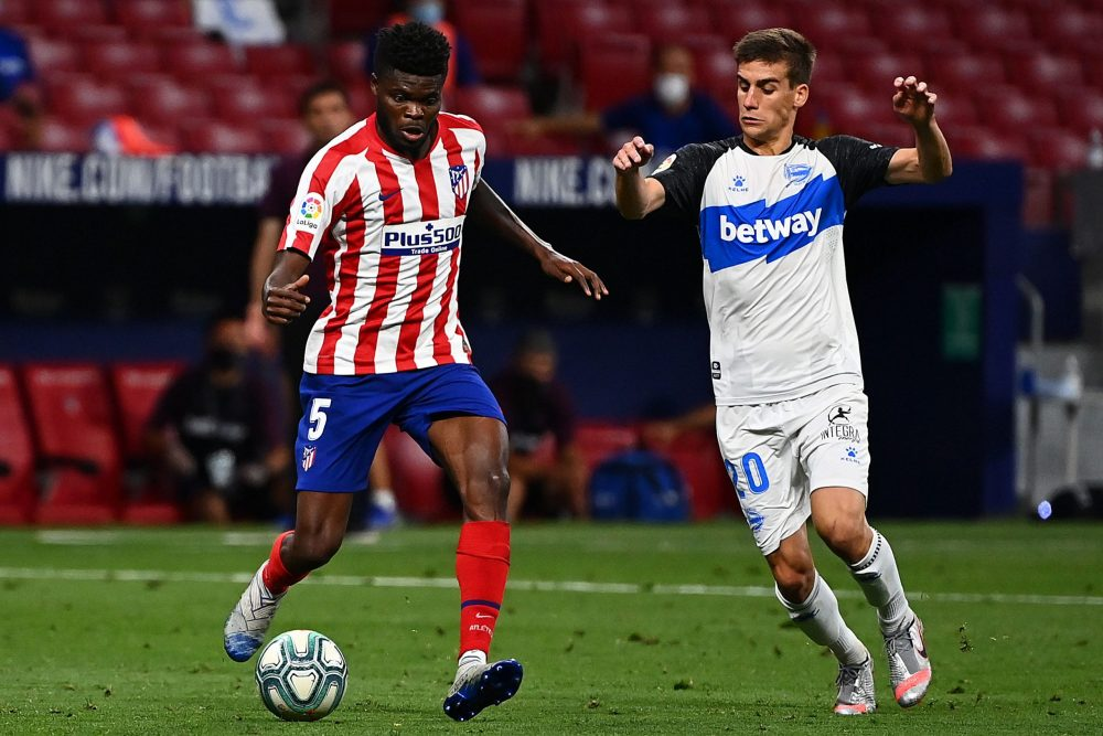 Alaves' Spanish midfielder Pere Pons (R) challenges Atletico Madrid's Ghanaian midfielder Thomas Partey during the Spanish League football match between Atletico Madrid and Alaves at the Wanda Metropolitan stadium in Madrid on June 27, 2020. (Photo by Gabriel BOUYS / AFP) (Photo by GABRIEL BOUYS/AFP via Getty Images)