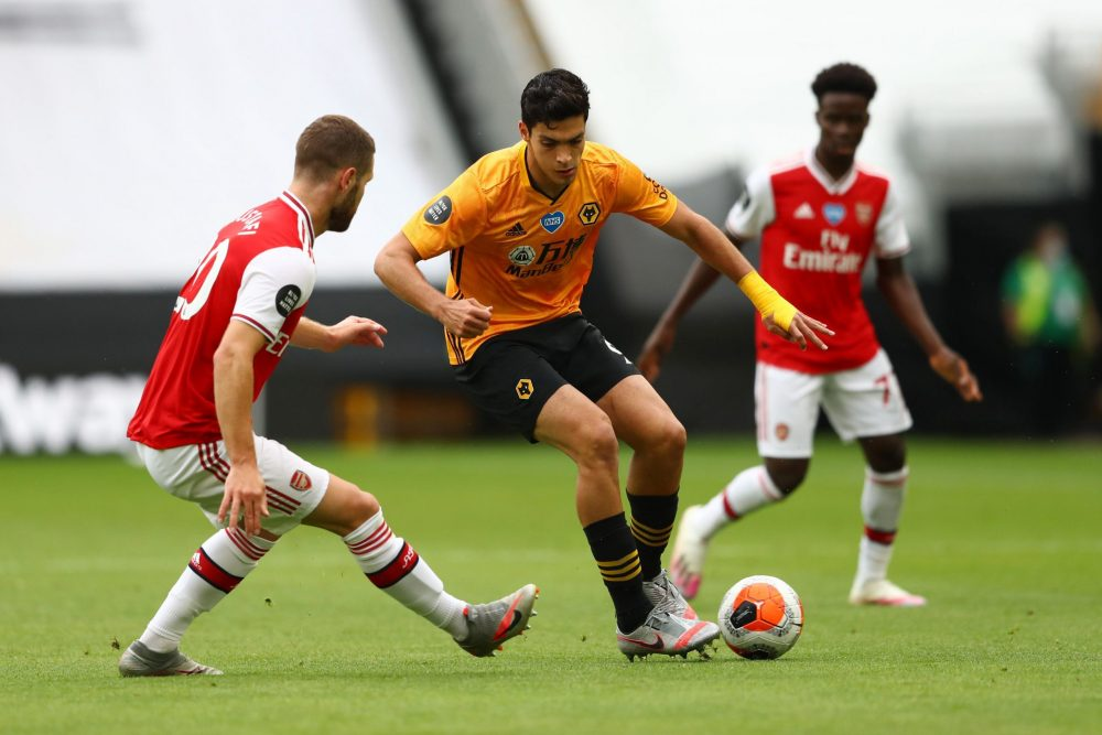 WOLVERHAMPTON, ENGLAND - JULY 04: Shkodran Mustafi of Arsenal and Raul Jimenez of Wolverhampton Wanderers battle for the ball during the Premier League match between Wolverhampton Wanderers and Arsenal FC at Molineux on July 04, 2020 in Wolverhampton, England. Football Stadiums around Europe remain empty due to the Coronavirus Pandemic as Government social distancing laws prohibit fans inside venues resulting in all fixtures being played behind closed doors. (Photo by Michael Steele/Getty Images)