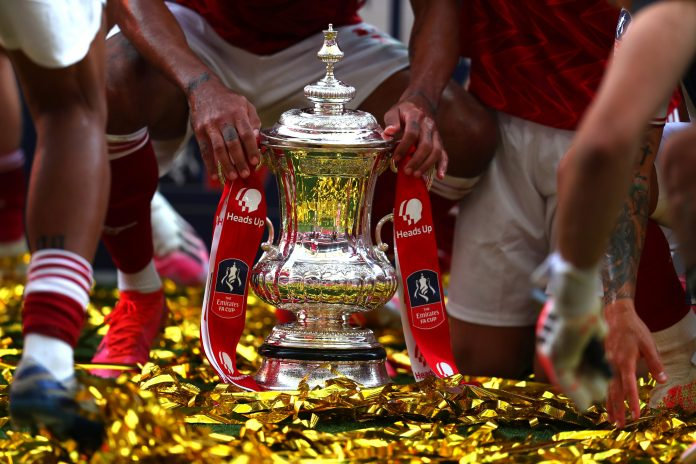 All that glitters isn't always gold: LONDON, ENGLAND - AUGUST 01: Detailed view of the FA Cup Trophy as it sits in the pitch surrounded by Arsenal players after the FA Cup Final match between Arsenal and Chelsea at Wembley Stadium on August 01, 2020 in London, England. Football Stadiums around Europe remain empty due to the Coronavirus Pandemic as Government social distancing laws prohibit fans inside venues resulting in all fixtures being played behind closed doors. (Photo by Catherine Ivill/Getty Images)