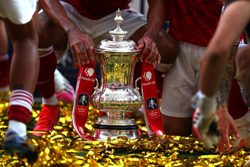LONDON, ENGLAND - AUGUST 01: Detailed view of the FA Cup Trophy as it sits in the pitch surrounded by Arsenal players after the FA Cup Final match between Arsenal and Chelsea at Wembley Stadium on August 01, 2020 in London, England. Football Stadiums around Europe remain empty due to the Coronavirus Pandemic as Government social distancing laws prohibit fans inside venues resulting in all fixtures being played behind closed doors. (Photo by Catherine Ivill/Getty Images)