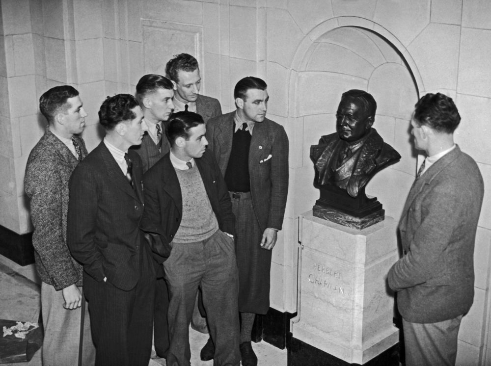 A group of Arsenal players admire a bronze memorial bust of the late club manager Herbert Chapman by Jacob Epstein, on display at the Arsenal Stadium in London, October 1936. Amongst them are Herbert Roberts, Eddie Hapgood, Bobby Davidson, Jack Crayston and Frank Moss. (Photo by Topical Press Agency/Hulton Archive/Getty Images)
