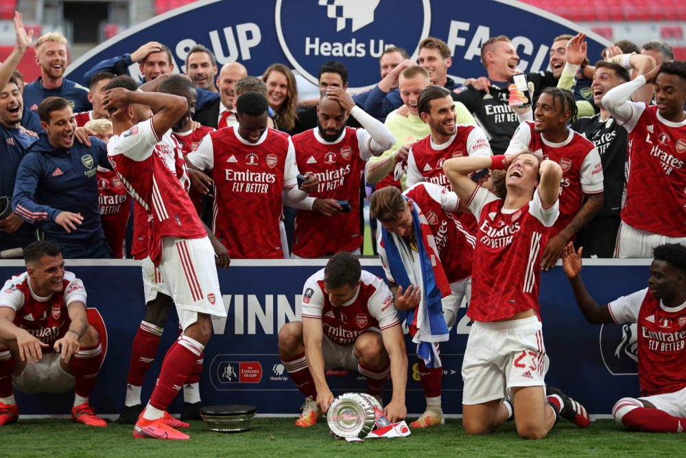Arsenal's Gabonese striker Pierre-Emerick Aubameyang (L) reacts as he drops the winner's trophy as the team celebrates victory after the English FA Cup final football match between Arsenal and Chelsea at Wembley Stadium in London, on August 1, 2020. - Arsenal won the match 2-1. (Photo by Catherine Ivill / POOL / AFP)