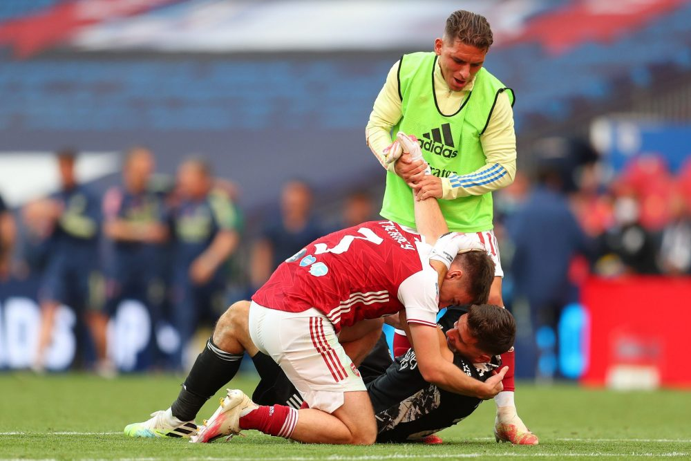 Arsenal's Argentinian goalkeeper Emiliano Martinez is mobbed by Arsenal's Scottish defender Kieran Tierney (L) after the English FA Cup final football match between Arsenal and Chelsea at Wembley Stadium in London, on August 1, 2020. - Arsenal won the match 2-1. (Photo by Catherine Ivill / POOL / AFP)