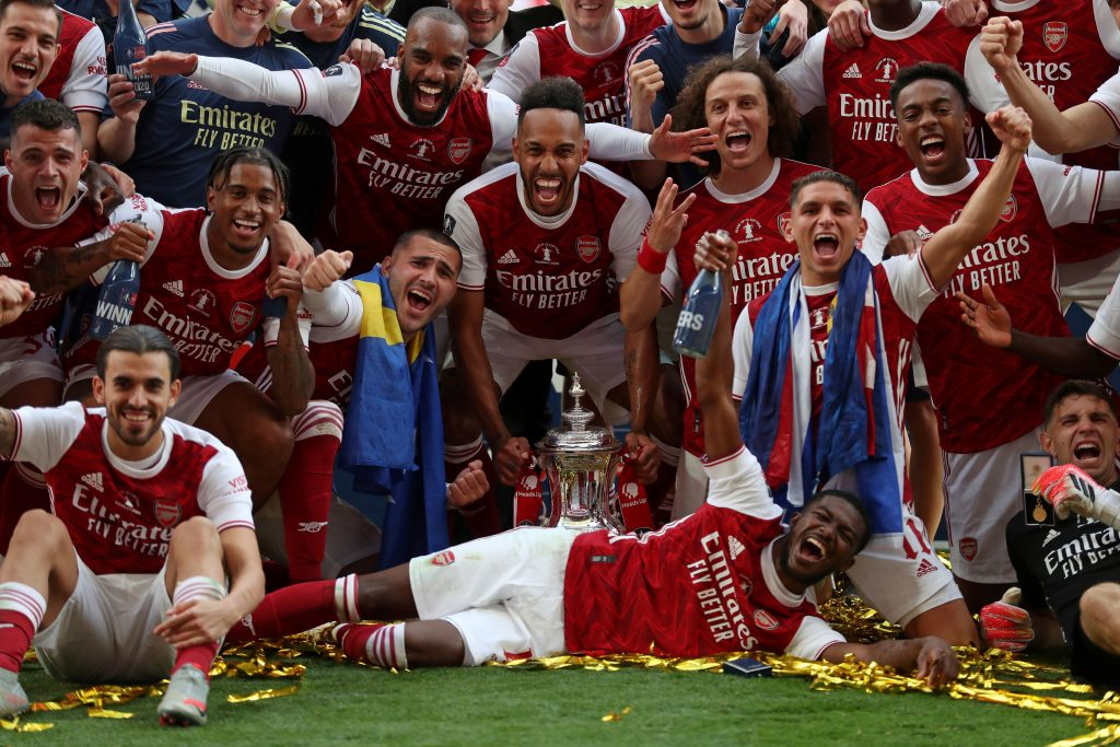 Arsenal's Gabonese striker Pierre-Emerick Aubameyang holds the winner's trophy as the team celebrates victory after the English FA Cup final football match between Arsenal and Chelsea at Wembley Stadium in London, on August 1, 2020. - Arsenal won the match 2-1. (Photo by Catherine Ivill / POOL / AFP)