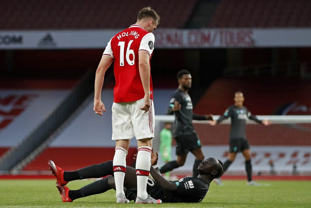 Arsenal's English defender Rob Holding (L) clashes with Liverpool's Senegalese striker Sadio Mane during the English Premier League football match between Arsenal and Liverpool at the Emirates Stadium in London on July 15, 2020. (Photo by PAUL CHILDS / POOL / AFP)