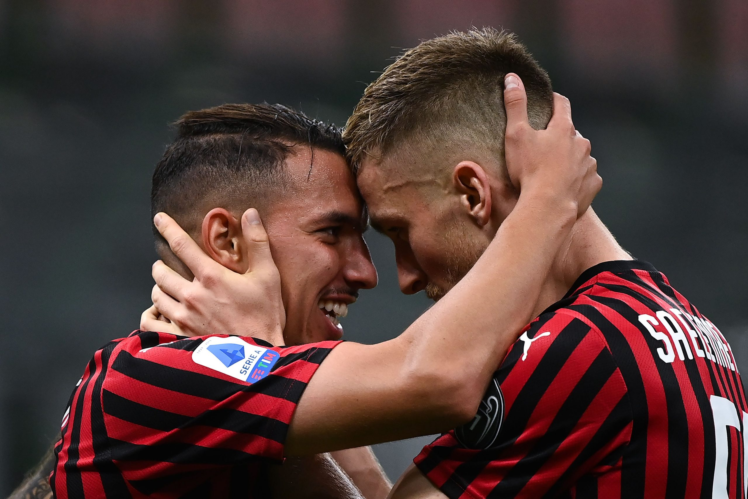 AC Milan's Algerian midfielder Ismael Bennacer (L) celebrates with AC Milan's Belgian midfielder Alexis Saelemaeker after scoring a goal during the Italian Serie A football match AC Milan vs Bologna played behind closed doors on July 15, 2020 at the San Siro Stadium in Milan, as the country eases its lockdown aimed at curbing the spread of the COVID-19 infection, caused by the novel coronavirus. (Photo by MARCO BERTORELLO / AFP)