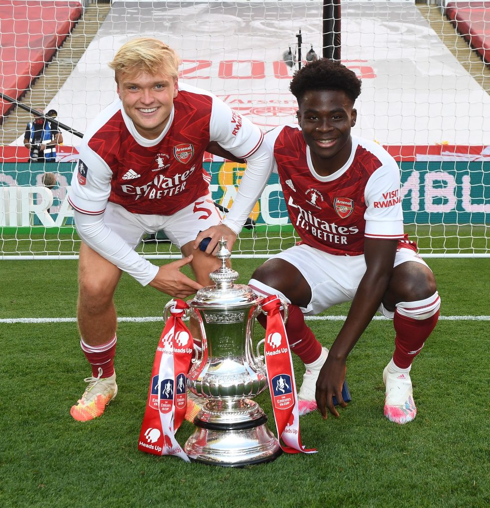 Matt Smith (L) and Bukayo Saka (R) with the FA Cup trophy (Photo via Arsenal on Twitter)