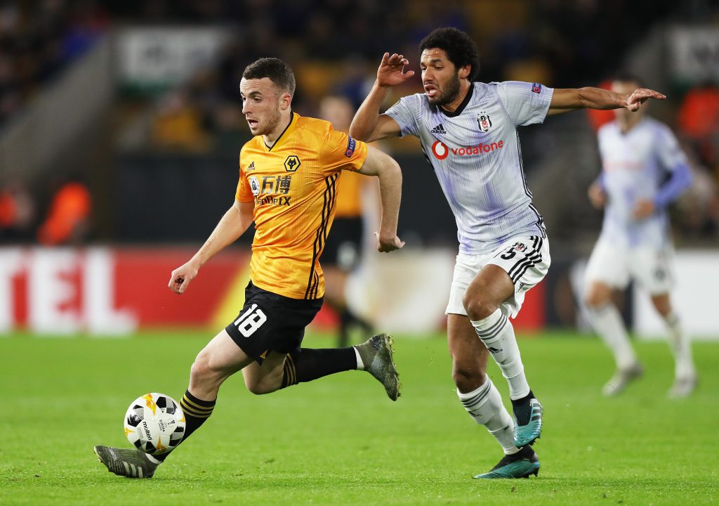 WOLVERHAMPTON, ENGLAND - DECEMBER 12: Diogo Jota of Wolverhampton Wanderers runs with the ball past Mohamed Elneny of Besiktas during the UEFA Europa League group K match between Wolverhampton Wanderers and Besiktas at Molineux on December 12, 2019 in Wolverhampton, United Kingdom. (Photo by David Rogers/Getty Images)