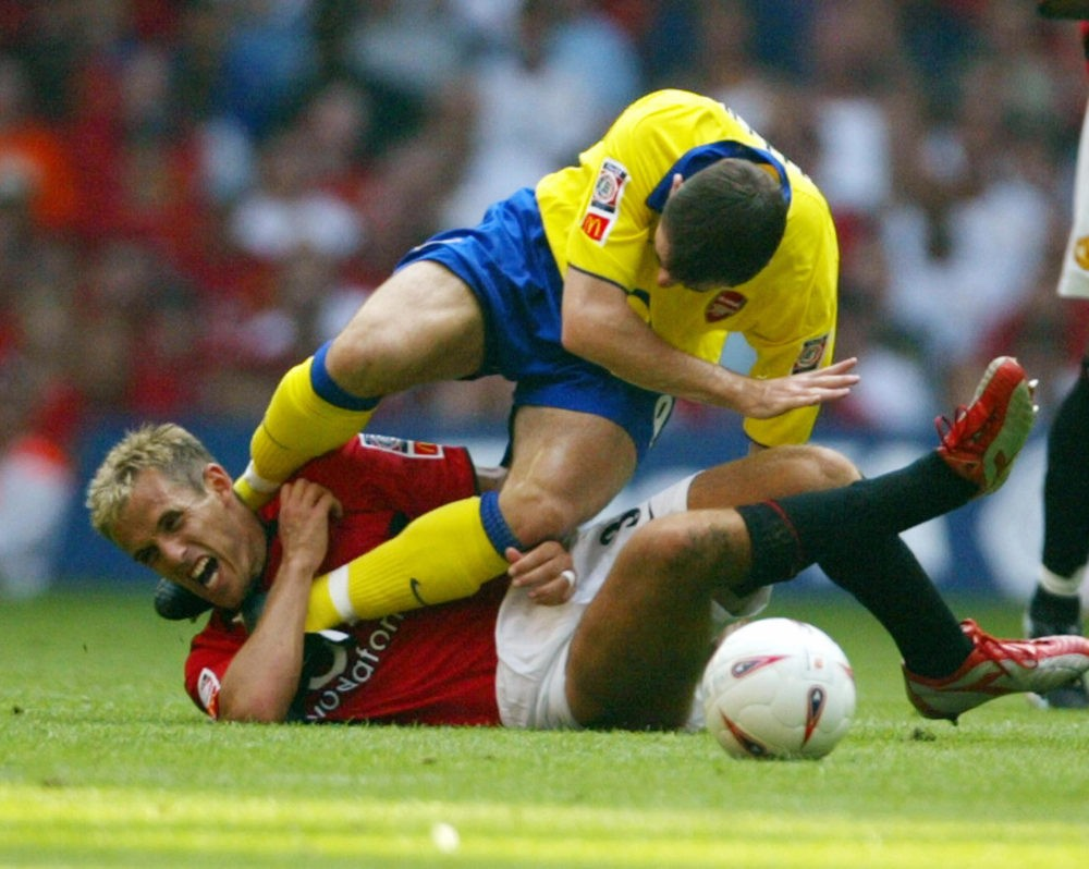 Arsenal's Francis Jeffers lands on Manchester United's Philip Neville after a hard tackle which resulted in a red card for Jeffers during the FA Community Shield soccer match 10 August, 2003 in Cardiff, Wales, UK. Manchester United and Arsenal tied one goal each with Manchester United winning on penalty kicks 5-4. AFP PHOTO/JIM WATSON