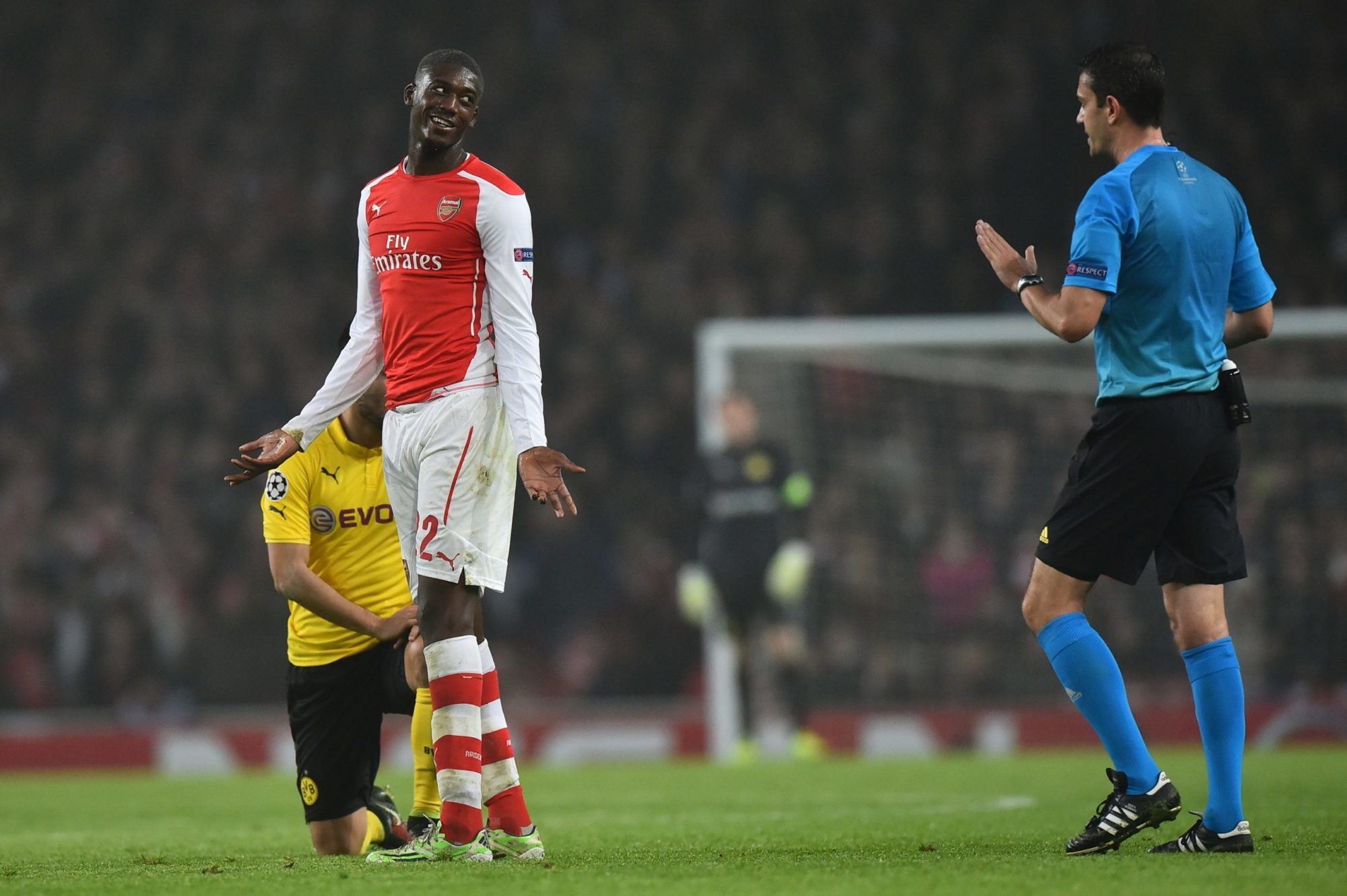 Arsenal's French striker Yaya Sanogo (2L) gestures to Hungarian referee Viktor Kassai (R) after bringing down Dortmund's German midfielder Ilkay Guendogan (L) during the UEFA Champions League Group D football match between Arsenal and Borussia Dortmund at the Emirates Stadium in north London on November 26, 2014. AFP PHOTO / BEN STANSALL