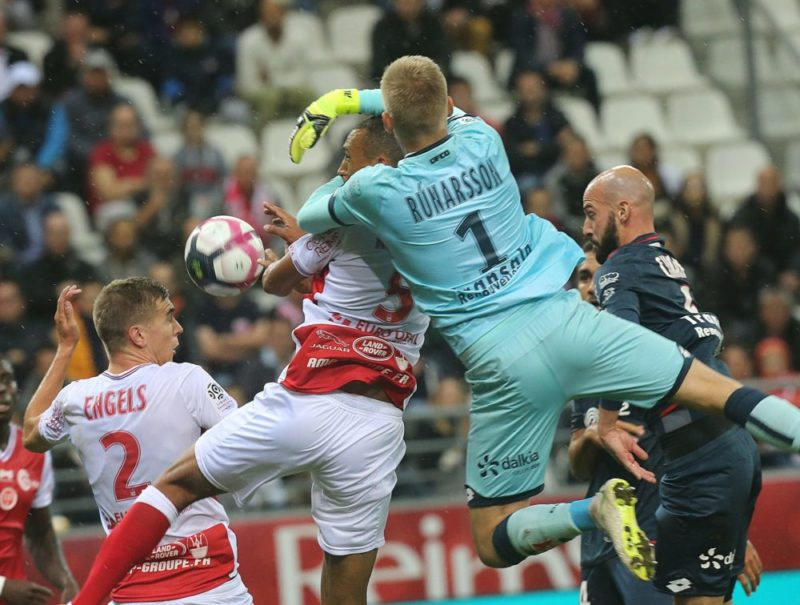 Reims' Moroccoan defender Yunis Abdedlhamid (L) vies with Dijon's Iceland goalkeeper Runar Alex Runarsson (R) during the French L1 football match between Reims and Dijon on September 22, 2018 at the Auguste Delaune Stadium in Reims. (Photo by FRANCOIS NASCIMBENI / AFP)
