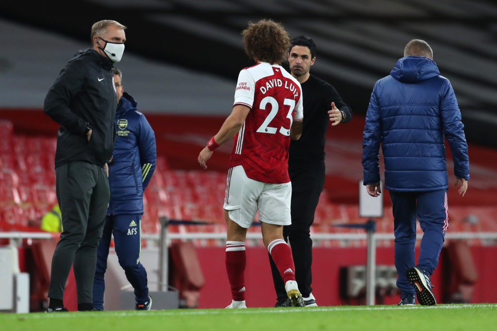LONDON, ENGLAND: David Luiz of Arsenal is embraced by Mikel Arteta, Manager of Arsenal as he is substituted off following an injury during the Premier League match between Arsenal and Leicester City at Emirates Stadium on October 25, 2020. (Photo by Catherine Ivill/Getty Images)