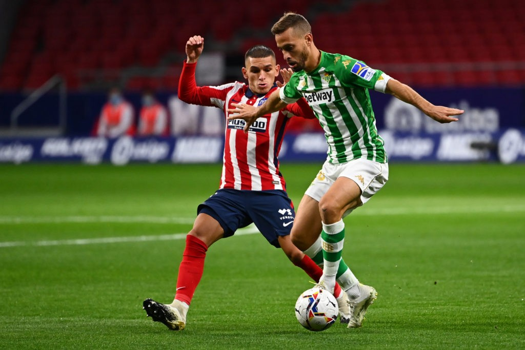 Atletico Madrid's Uruguayan midfielder Lucas Torreira (L) vies with Real Betis' Spanish midfielder Sergio Canales during the Spanish League football match between Atletico Madrid and Real Betis at the Wanda Metropolitan stadium in Madrid on October 24, 2020. (Photo by GABRIEL BOUYS/AFP via Getty Images)