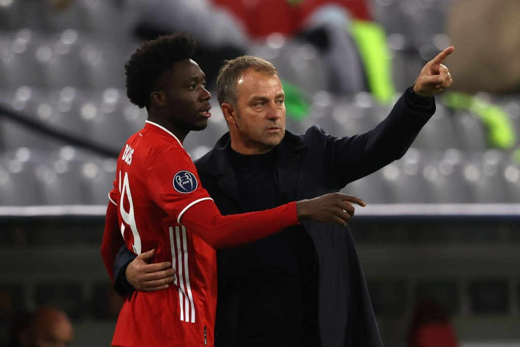 MUNICH, GERMANY - OCTOBER 21: Hans-Dieter Flick, head coach of FC Bayern München talks to his player Alphonso Davies during the UEFA Champions League Group A stage match between FC Bayern Muenchen and Atletico Madrid at Allianz Arena on October 21, 2020 in Munich, Germany. (Photo by Alexander Hassenstein/Getty Images)