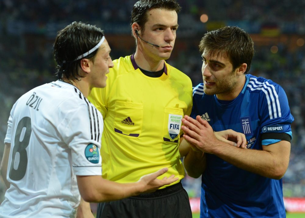 Greek defender Sokratis Papastathopoulos (R) argues with German midfielder Mesut Oezil during the Euro 2012 football championships quarter-final match Germany vs Greece on June 22, 2012 at the Gdansk Arena. Germany won 4 to 2. AFP PHOTO / CHRISTOF STACHE