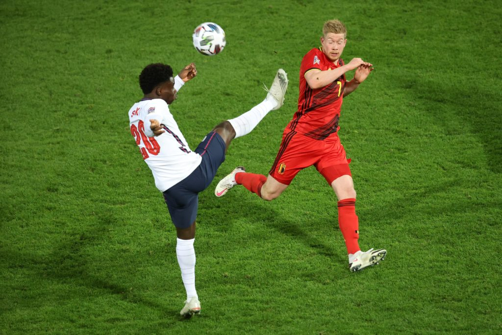 England's midfielder Bukayo Saka (L) and Belgium's Kevin De Bruyne fight for the ball during the UEFA Nations League football match between Belgium and England, on November 15, 2020 at Den Dreef stadium in Louvain. (Photo by VIRGINIE LEFOUR/BELGA/AFP via Getty Images)
