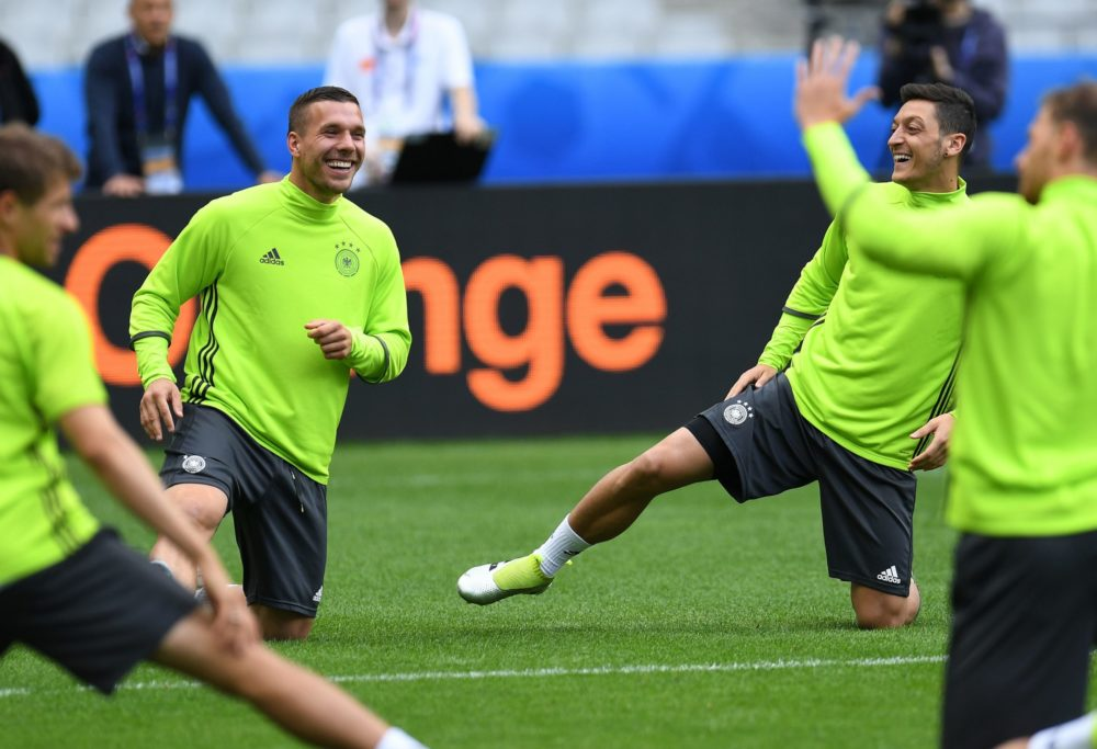 Germany's midfielder Lukas Podolski (L) and Germany's midfielder Mesut Oezil warm up during a training session at the stadium Stade de France in St.Denis , France on June 15, 2016 on the eve of the Euro 2016 football match between Germany and Poland. / AFP / PATRIK STOLLARZ