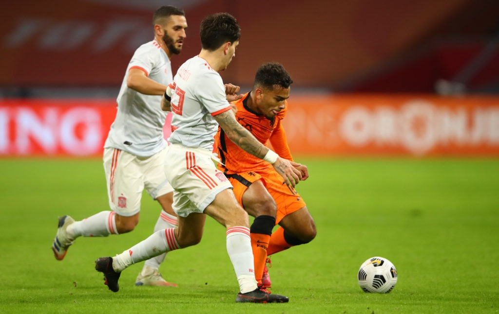 Netherlands' midfielder Owen Wijndal (R) fights for the ball with Spain's defender Hector Bellerin during the friendly football match between Netherlands and Spain at the Johan Cruijff ArenA in Amsterdam on November 11, 2020. (Photo by DEAN MOUHTAROPOULOS/POOL/AFP via Getty Images)