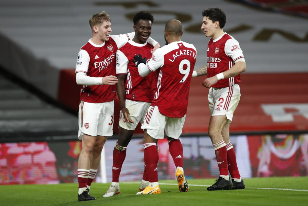 LONDON, ENGLAND - DECEMBER 26: Bukayo Saka of Arsenal celebrates with teammates Emile Smith Rowe, Alexandre Lacazette, and Hector Bellerin after scoring his team's third goal during the Premier League match between Arsenal and Chelsea at Emirates Stadium on December 26, 2020 in London, England. The match will be played without fans, behind closed doors as a Covid-19 precaution. (Photo by Andrew Boyers - Pool/Getty Images)
