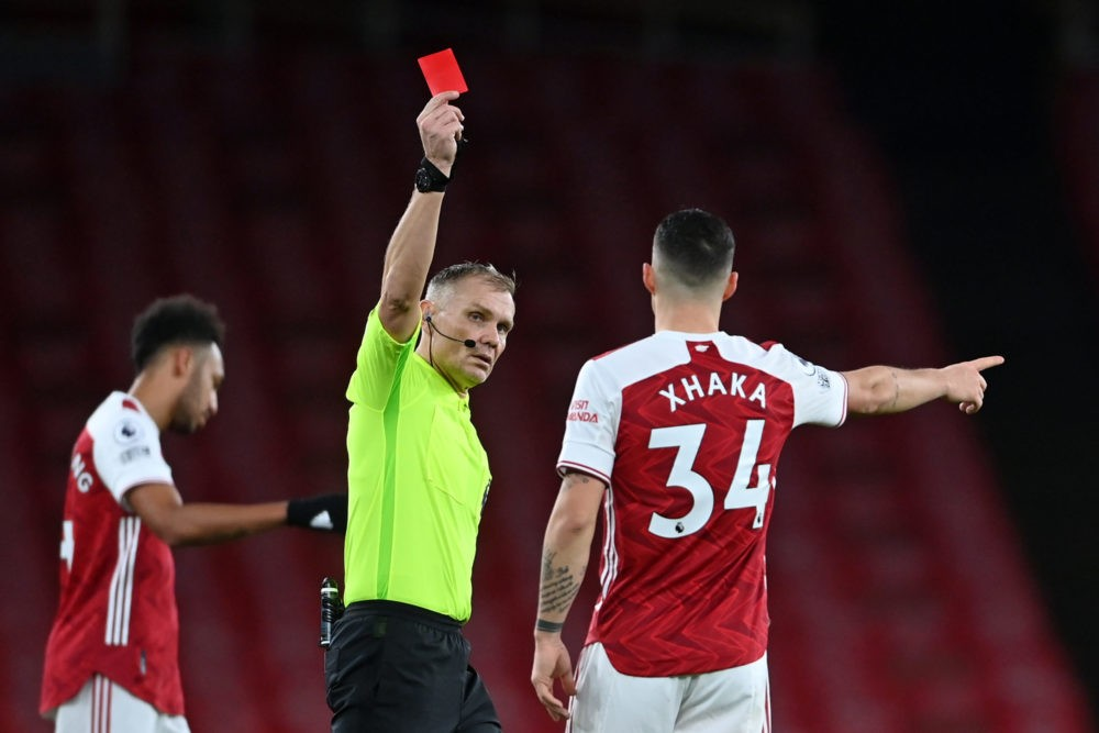 Referee Graham Scott shows the red card to send off Arsenal's Swiss midfielder Granit Xhaka (R) during the English Premier League football match between Arsenal and Burnley at the Emirates Stadium in London on December 13, 2020. (Photo by Laurence Griffiths / POOL / AFP)