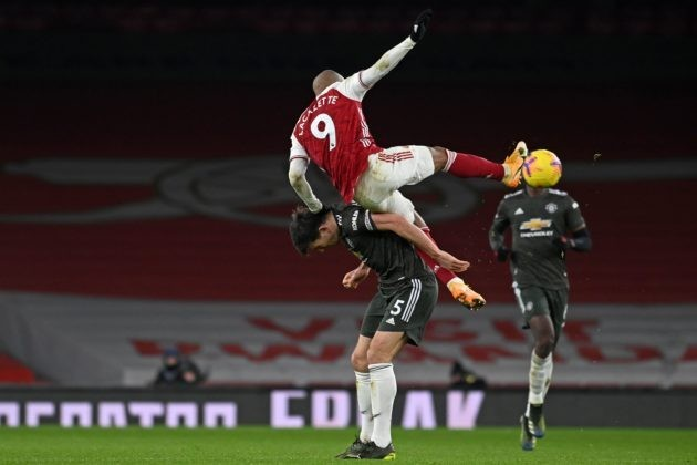 Manchester United's English defender Harry Maguire vies with Arsenal's French striker Alexandre Lacazette (up) during the English Premier League football match between Arsenal and Manchester United at the Emirates Stadium in London on January 30, 2021. (Photo by Andy Rain / POOL / AFP)