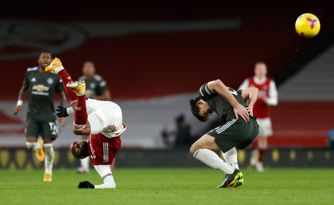 Arsenal's French striker Alexandre Lacazette (L) clashes with Manchester United's English defender Harry Maguire during the English Premier League football match between Arsenal and Manchester United at the Emirates Stadium in London on January 30, 2021. (Photo by Ian KINGTON / IKIMAGES / AFP)
