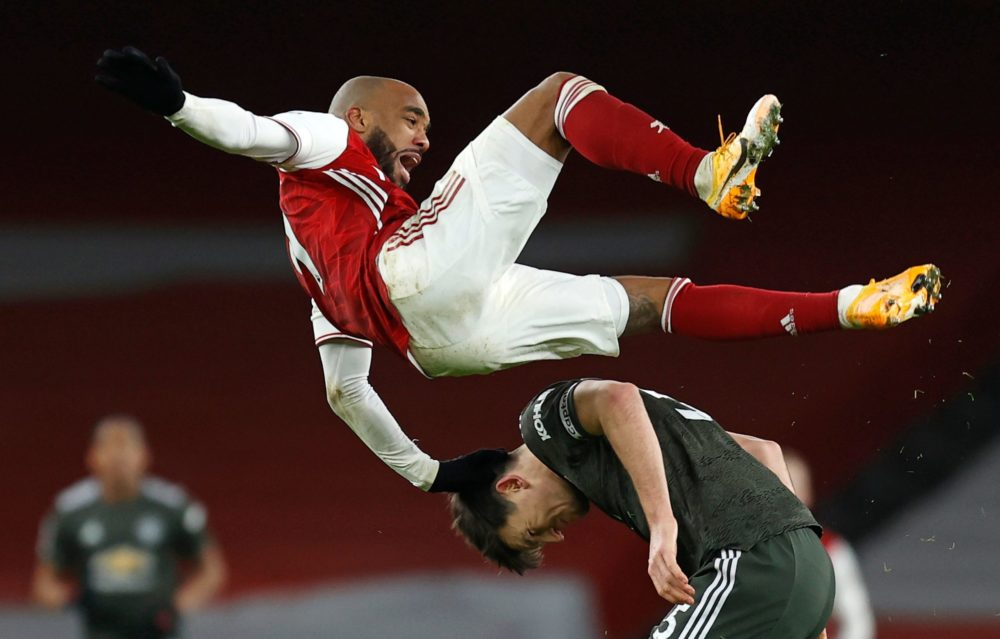 Arsenal's French striker Alexandre Lacazette (top) clashes with Manchester United's English defender Harry Maguire during the English Premier League football match between Arsenal and Manchester United at the Emirates Stadium in London on January 30, 2021. (Photo by Ian KINGTON / IKIMAGES / AFP)