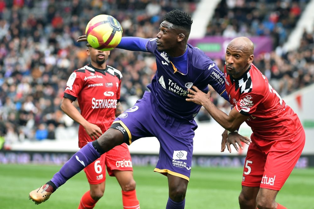 Toulouse's French forward Yaya Sanogo (C) controls the ball during the French L1 football match between Toulouse and Guingamp on March 10, 2019, at the municipal stadium in Toulouse, southwestern France. (Photo by REMY GABALDA / AFP)