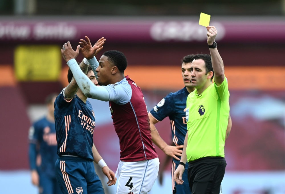 BIRMINGHAM, ENGLAND - FEBRUARY 06: Referee Chris Kavanagh awards Ezri Konsa of Aston Villa a yellow card during the Premier League match between Aston Villa and Arsenal at Villa Park on February 06, 2021 in Birmingham, England. Sporting stadiums around the UK remain under strict restrictions due to the Coronavirus Pandemic as Government social distancing laws prohibit fans inside venues resulting in games being played behind closed doors. (Photo by Shaun Botterill/Getty Images)