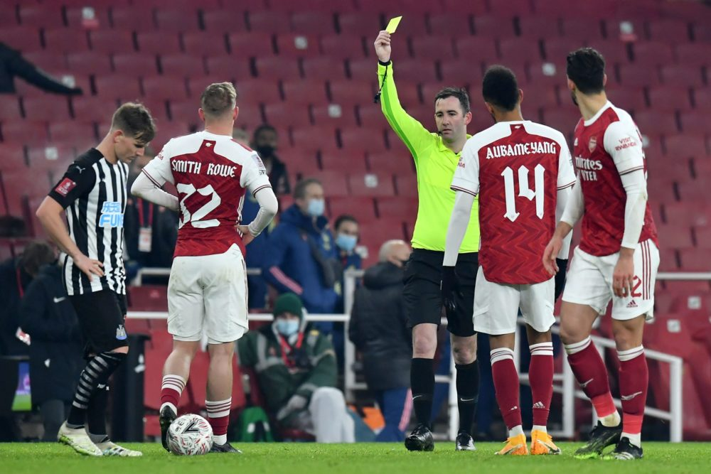 English referee Chris Kavanagh shows a yellow card to Arsenal's English midfielder Emile Smith Rowe after reviewing his initial red card during the English FA Cup third round football match between Arsenal and Newcastle United at the Emirates Stadium in London on January 9, 2021. (Photo by Glyn KIRK / AFP)