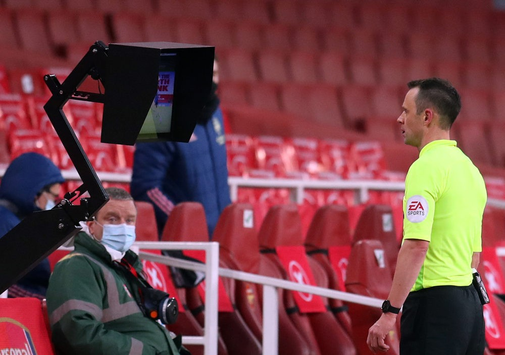 Referee Stuart Attwell views a VAR screen after Leeds United's Liam Cooper fouled Arsenal's English striker Bukayo Saka during the English Premier League football match between Arsenal and Leeds United at the Emirates Stadium in London on February 14, 2021. (Photo by CATHERINE IVILL/POOL/AFP via Getty Images)