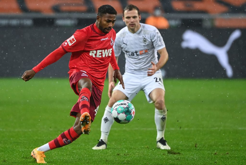 Cologne's Nigerian forward Emmanuel Dennis plays the ball in front of Moenchengladbach's German defender Tony Jantschke during the German first division Bundesliga football match between Borussia Moenchengladbach and 1 FC Cologne in Moenchengladbach, western Germany, on February 6, 2021. (Photo by INA FASSBENDER/AFP via Getty Images)