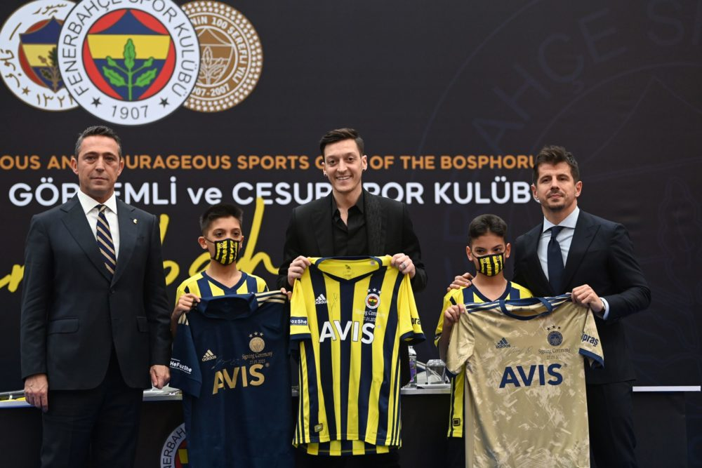 TOPSHOT - German midfielder Mesut Ozil (C) holds his new jersey as he poses with Fenerbahce's president Ali Koc (L) and sport director Emre Belezoglu (R), during a press conference after he signed his new three-and-a-half year contract with Turkish football club Fenerbahce at the Divan Faruk ilgaz facilities on January 27, 2021 in Istanbul. (Photo by Ozan KOSE / AFP) (Photo by OZAN KOSE/AFP via Getty Images)