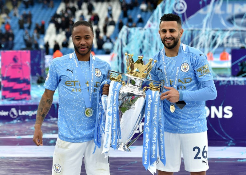 Raheem Sterling left and Riyad Mahrez pose with the trophy after the Premier League match at the Etihad Stadium, Manchester. Picture date: Sunday May 23, 2021.