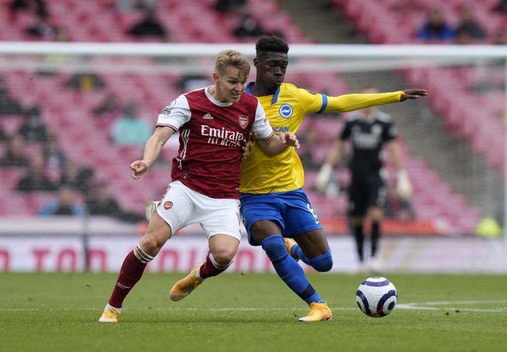 Arsenal's Martin Odegaard and Brighton and Hove Albion's Yves Bissouma battle for the ball during the Premier League match at the Emirates Stadium, London. Picture date: Sunday, May 23, 2021. Copyright: Alastair Grant