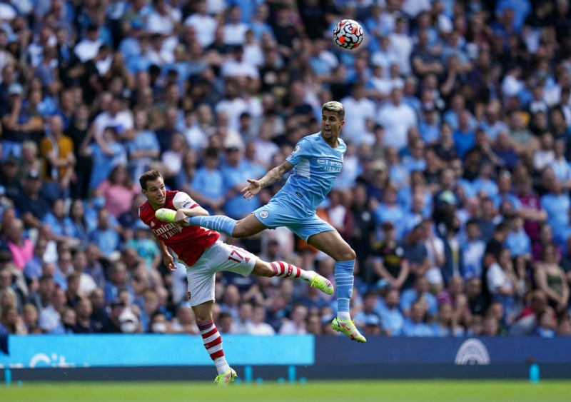 Manchester City v Arsenal - Premier League - Etihad Stadium Arsenals Cedric Soares left and Manchester City s Joao Cancelo battle for the ball in the air during the Premier League match at the Etihad Stadium, Manchester. Picture date: Saturday August 28, 2021. Copyright: Nick Potts